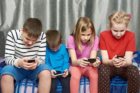 Дети играют игру на мобильных телефонах на дому