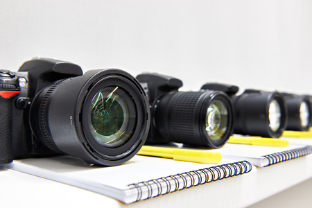 reflex: Reflex digital cameras with notepad in the classroom photoschool close-up