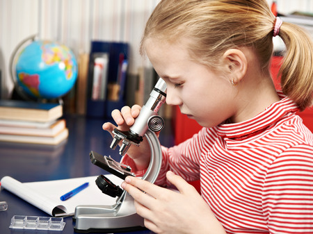 Girl looking through a microscope at home learning table photo