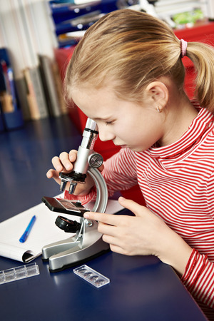 solidified: Girl looking through a microscope at home learning table