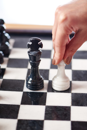 pawn king: Hand with white pawn moves to black king closeup Stock Photo