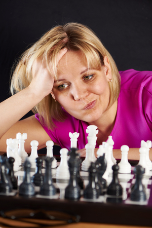 Woman playing chess on black background photo