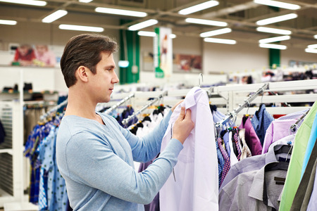 tienda de ropa: El hombre elige una camisa en la tienda