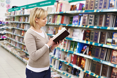 business book: Woman chooses a book in the store Stock Photo