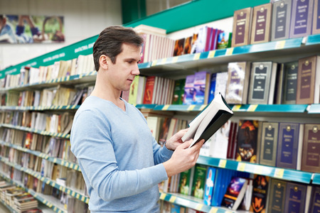 origin of man: Man chooses a book in the store Stock Photo