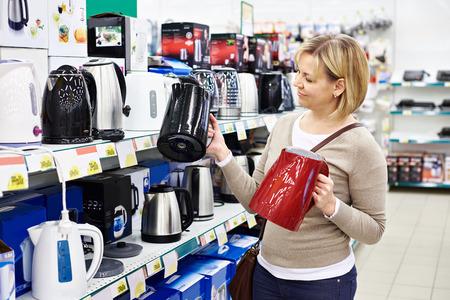 gospodarstwo domowe: Kobieta gospodyni zakupy czajnik elektryczny, uśmiechając Zdjęcie Seryjne