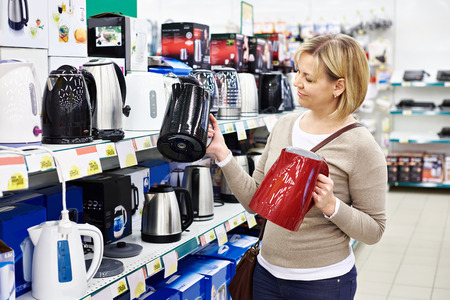 electric kettle: Woman housewife shopping for electric kettle, smiling