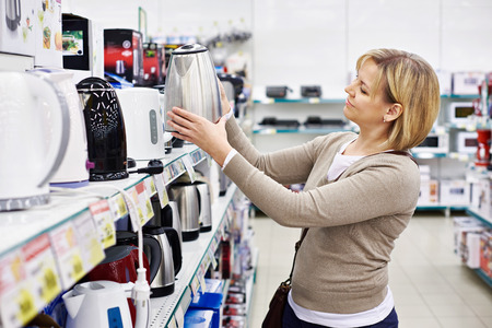electronic store: Woman housewife shopping for electric kettle, smiling