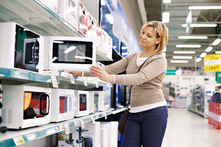 home appliance: Woman housewife shopping for microwave oven, smiling