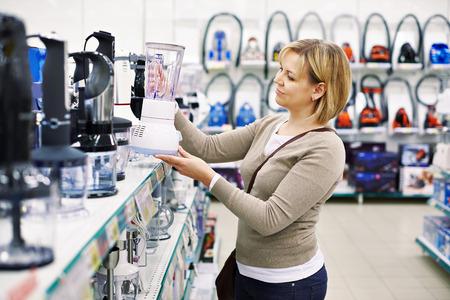 De vrouw kiest een blender in de winkel