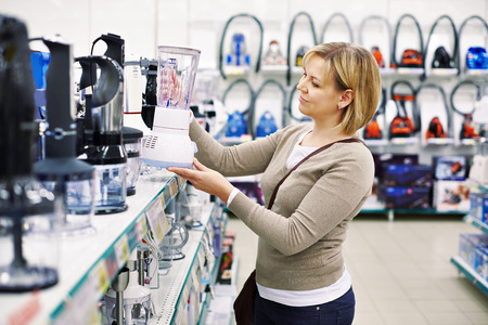 home appliance: Woman chooses a blender in the store Stock Photo