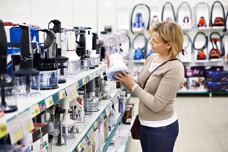 Женщина выбирает блендер в магазине
