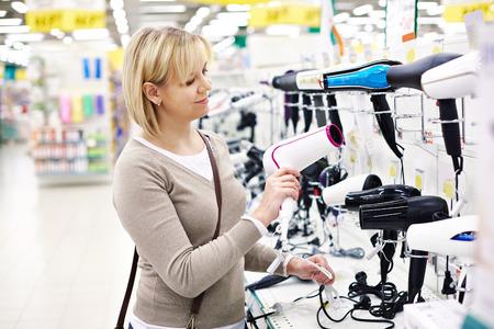 Женщина выбирает фен в магазине