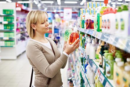 Woman chooses fragrant liquid soap in the store Banco de Imagens