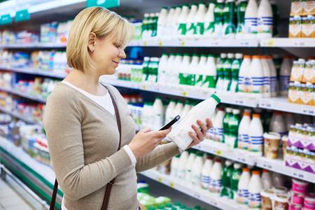 gamme de produit: Femme avec le mobile lait t�l�phone shopping � l'�picerie