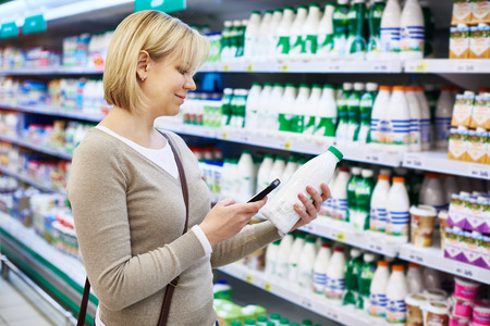 Woman with mobile phone shopping milk in grocery store