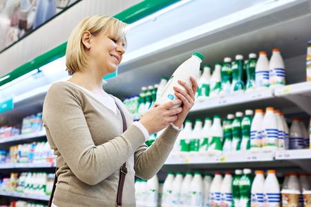 Женщина торговый молока в продуктовом магазине
