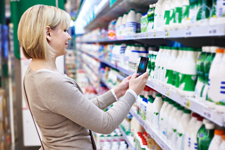 grocery shopper: Woman photographing with smartphone label of dairy products in shop