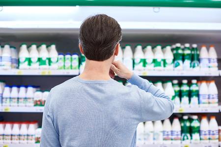dairy: El hombre elige los productos lácteos en la tienda