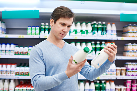 Man chooses dairy products in the store