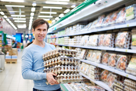 Человек покупает яйца в магазине