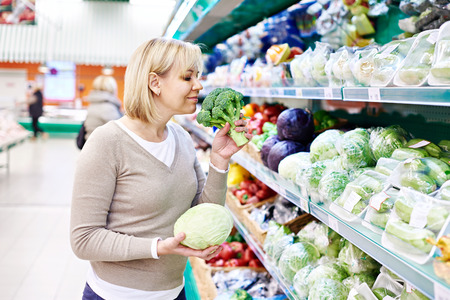 Woman sniffs broccoli and holds white cabbage in the store photo