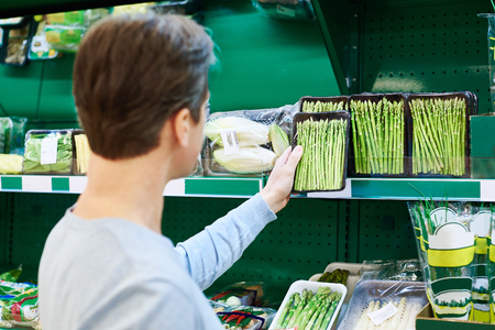 Man buys a asparagus in the store