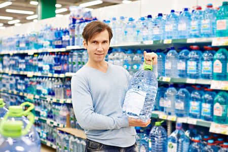 Man with big bottle drinking water in shop photo