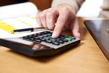Женская рука с помощью калькулятора Фото со стока