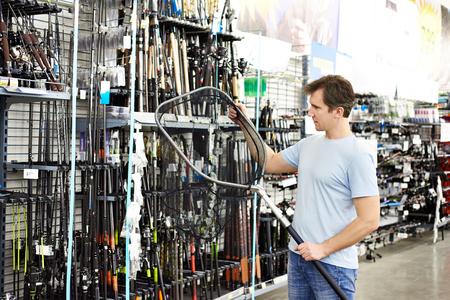 Человек выбирает целевую сеть для рыбной ловли в спортивном магазине Фото со стока