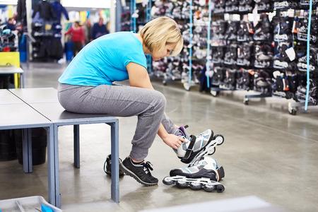 Woman wears roller skates in the sports shop