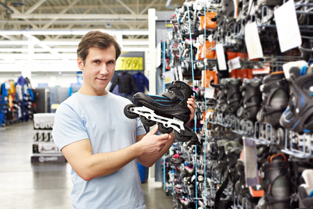Man chooses roller skates in the sports shop