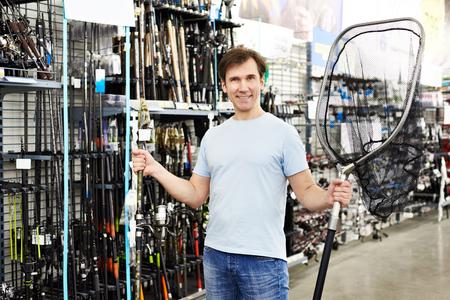 Человек выбирает целевую сеть для ловли в спортивном магазине Фото со стока