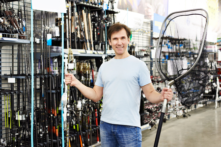 Man chooses landing net for fishing in the sports shop