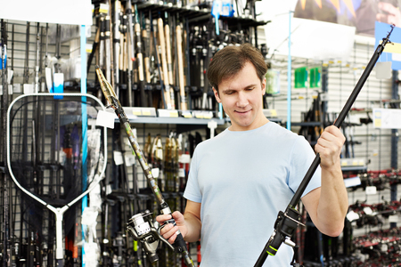 fishing tackle: Man chooses fishing rod in the sports shop Stock Photo