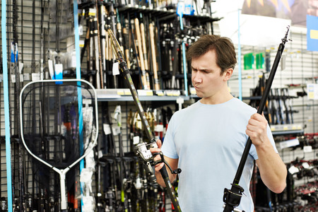 Man chooses fishing rod in the sports shop 스톡 콘텐츠