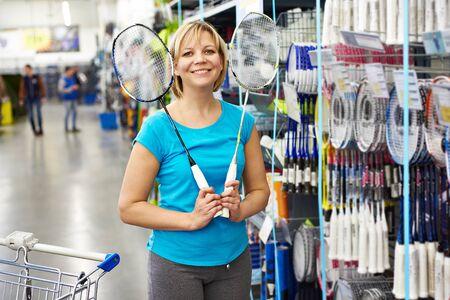 Woman chooses badminton racquet in sport shop