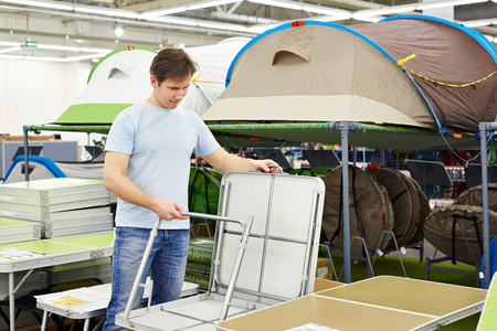 holidays vacancy: man chooses a folding camp table in the store leisure goods