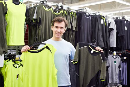 Happy man chooses for t-shirts in sport shop