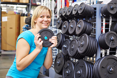 loads: Happy woman chooses loads for dumbbell in the sports shop Stock Photo