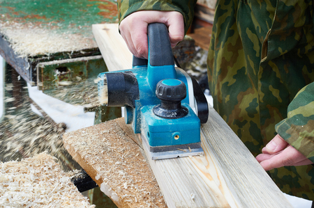 handtool: Carpenter with electric plane outdoors