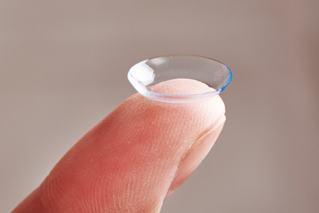 Medicine and vision - womans finger with contact lens