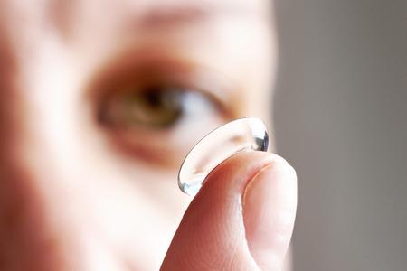 Медицина и видение - молодая женщина с контактной линзы