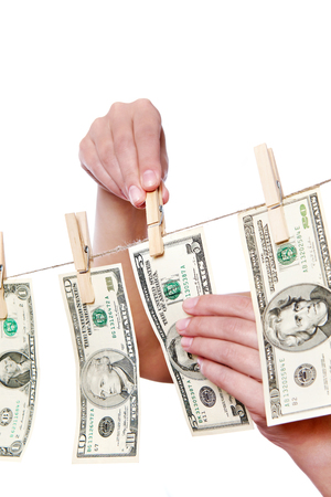 Hand pinch money on clothes line isolated