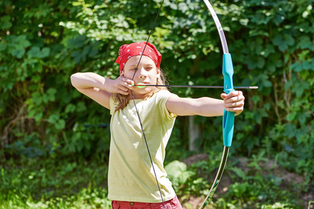 Girl with bow shooting to sport aim in sunny summer day