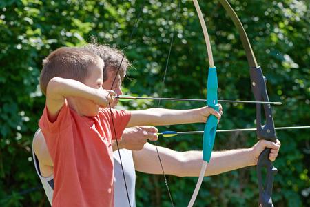 Маленький мальчик и мужчина с большой стрельбе из лука в солнечный летний день