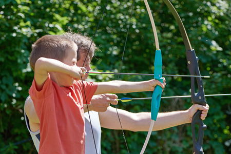 sport training: Little boy and man with big bow shooting in sunny summer day