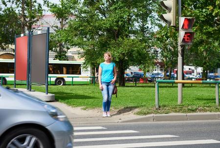 semaforo peatonal: Joven mujer se encuentra en un semáforo ya la espera de la señal verde Foto de archivo