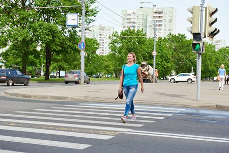 semaforo peatonal: Mujer joven que cruza la carretera en la luz verde