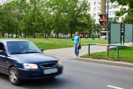 semaforo peatonal: Joven mujer se encuentra en un sem�foro ya la espera de la se�al verde Foto de archivo